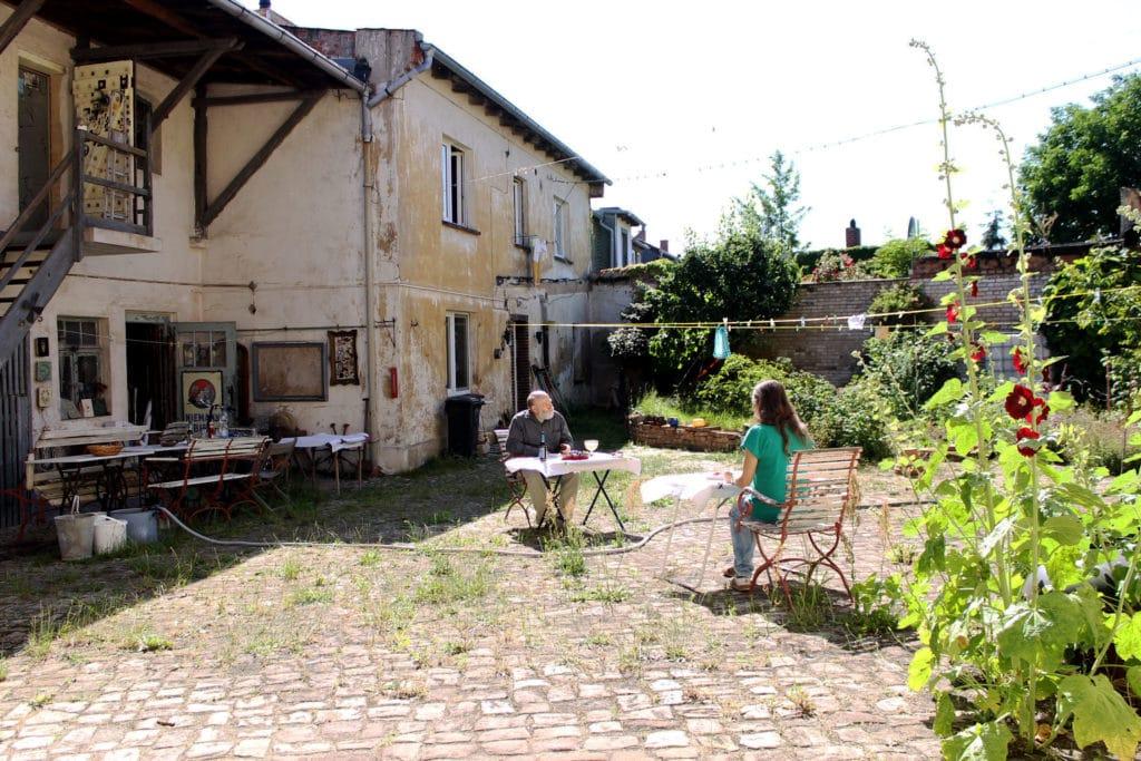 Zwei Personen sitzen in einem Hof und essen in der Mittagssonne zu Mittag. Sie sitzen an zwei getrennten Tischen gegenüber mit 1,5 Meter Abstand. Bild: Milena Giskes