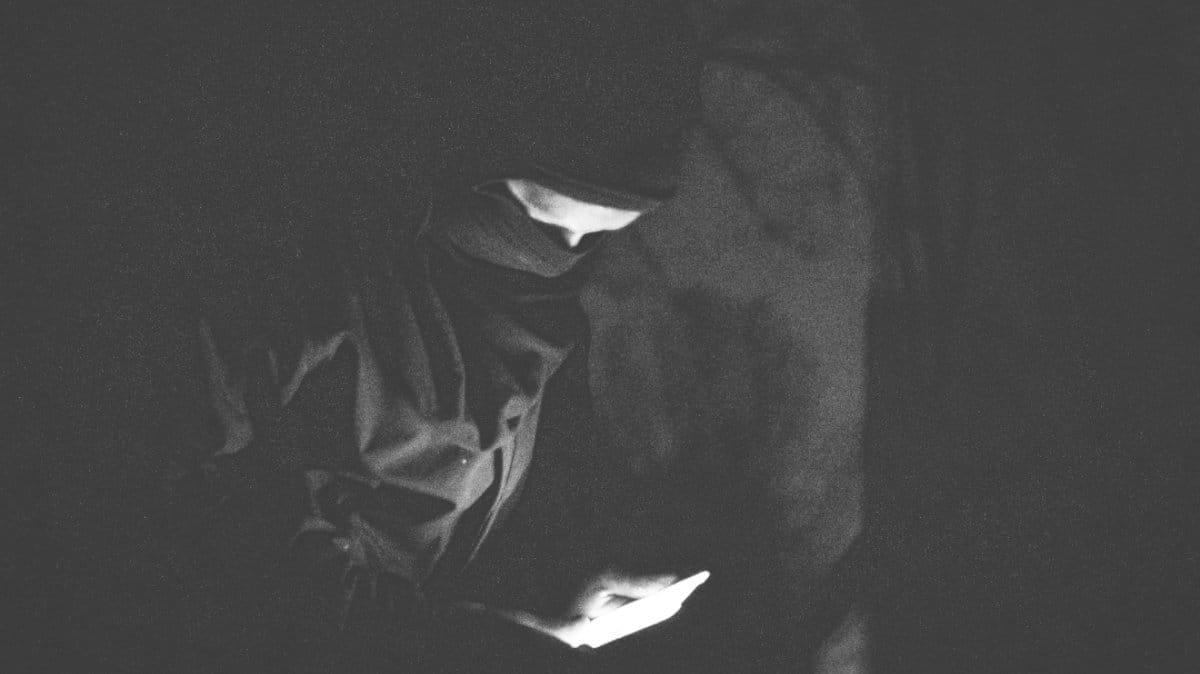 Ein Schwarz-Weiß-Photo einer Person, die in der Dunkelheit steht und auf ihr Handy schaut. Das Gesicht ist erleuchtet.